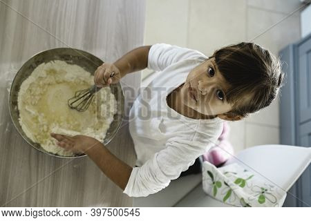 Little Cute Girl Is Cooking On Kitchen While Looking Above At Camera - Having Fun While Making Pizza