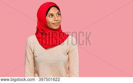 Young african american woman wearing traditional islamic hijab scarf smiling looking to the side and staring away thinking.