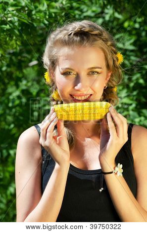 Close-up outdoor portrait of young beauty woman eating corn-cob