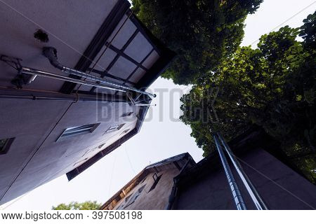From below residential buildings with pipes and green trees located against cloudless sky on street of town in summer