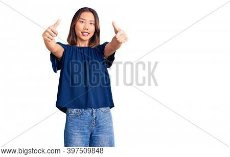 Young beautiful chinese girl wearing casual clothes approving doing positive gesture with hand, thumbs up smiling and happy for success. winner gesture.