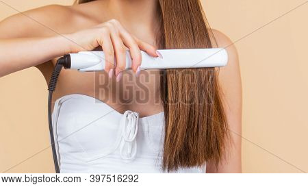 Girl Using Styler On Her Shining Hair. Hairstyle. Woman Ironing Long Hair With Flat Iron. Young Woma