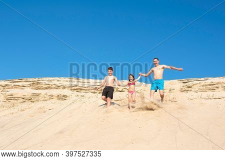 Happy Family Running On The Beach Sand On A Sunny Summer Day. Family Games On Vacation. Lifestyle