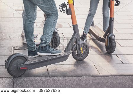Unrecognizable Youth Riding On Kick Scooters Outdoors, Legs On The Kick Scooter Closeup. Healthy Lif
