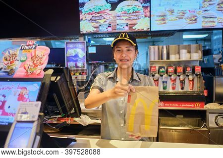 Bangkok, Thailand - Dec 3, 2019: Young Part-time Student Workers Smiling While Handing Mcdonald's Br