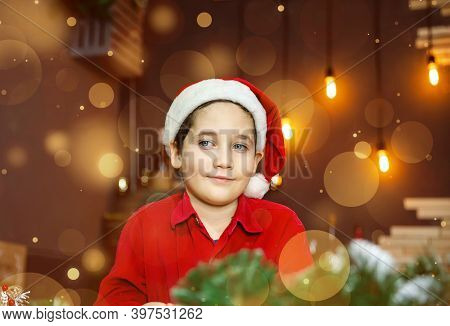 Beautiful Cute Boy In Santa Claus Cap On Blurred Golden Background With Lights. Christmas Time, Atmo