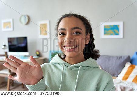Happy African Gen Z Teen Girl Waving Hand Talking To Camera In Bedroom. Mixed Race Teenager Recordin