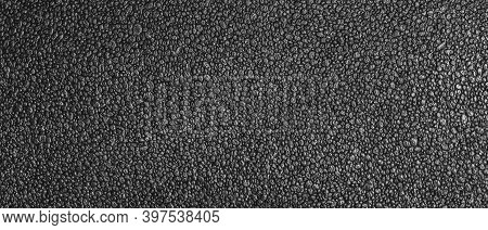 Panoramic View Of The Texture Of Dark Packaging Foam. Close-up Of The Foam Surface.