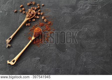 Two Spoons With Coffee On A Black Background. One Spoon With Coffee Beans. Second Spoon With Ground