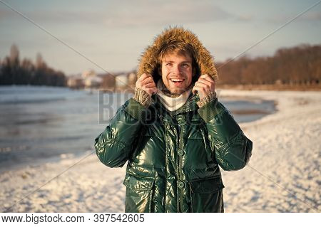 Travel And Vacation Concept. Man Warm Jacket Snowy Nature Background. Wind Resistant Clothes. Winter