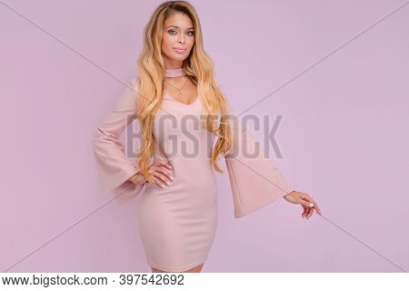 Portrait Of Beautiful Sexy Blonde Girl With Long Hair And Tanned Body Wearing Pink Dress Sensual Pos