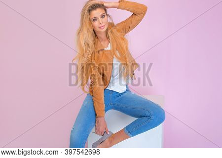 Beautiful Sexy Blonde Girl With Long Hair And Tanned Body Wearing Brown Jacket And Blue Jeans, Sitti