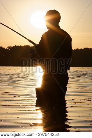 Silhouette Of Angler In The Rays Of The Rising Sun