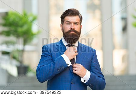 Customize Your Ensemble With Tie. Bearded Man Fix Necktie Wearing Blue Suit Outdoors. Classic Fashio