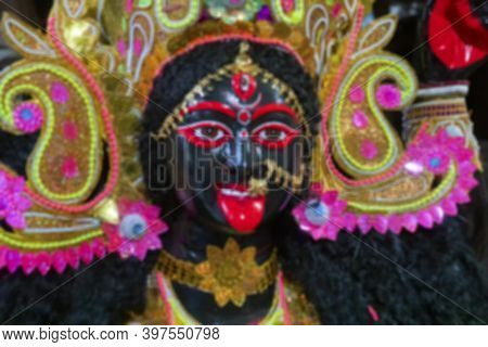 Blurred Image Of Painted Idol Of Goddess Kali With Black Face And Red Tongue. Goddess Of Time, Creat