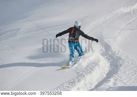 VALMOREL, FRANCE -CIRCA 2019: Anowboarder coming down fast in fresh powder snow off-piste free ride. Plowing snow