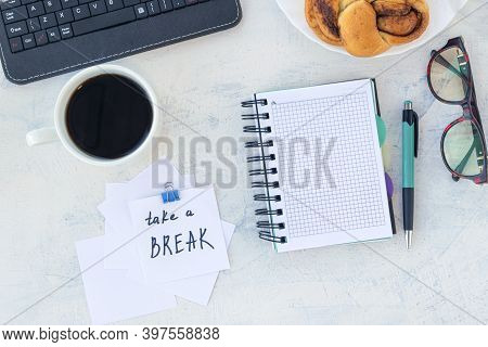 Take A Break. Concept Time Off. Words Take A Break In Stiker On The Working Table With Cup Of Coffee