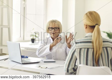 Senior Female Doctor Tells And Explains To The Patient His Diagnosis During The Consultation.