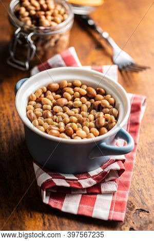 Mix of legume beans and chickpeas with sauce in a pot.