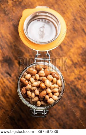 Mix of legume beans and chickpeas with sauce in jar. Top view.