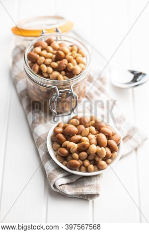 Mix of legume beans and chickpeas with sauce in bowl.