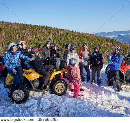 Group Of Cheerful People Sitting On Four-wheelers Atv, Enjoying Beautiful Winter Day In Snowy Mounta