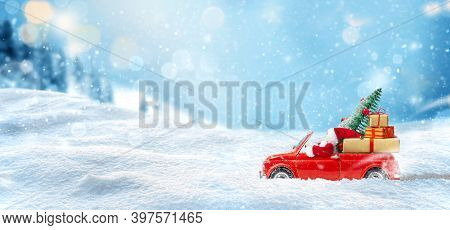 Santa Claus Drives The Red Toy Car And Delivers Presents And Christmas Tree At Snowy Background. Chr