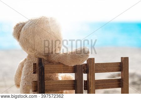 Teddy Bear Sit On Wooden Chair With Sea View. Love And Relationship Concept. Beautiful White Sandy B