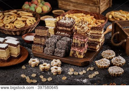 Still Life Of Assorted Different Mini Cakes With Cream And Chocolate