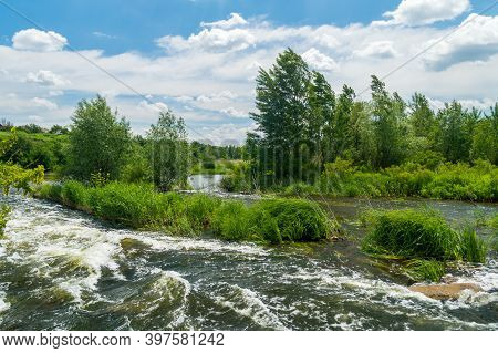 Flowing River Stream Of Water In The Rocks With Blue Sky. Water Flows A Torrent In The River
