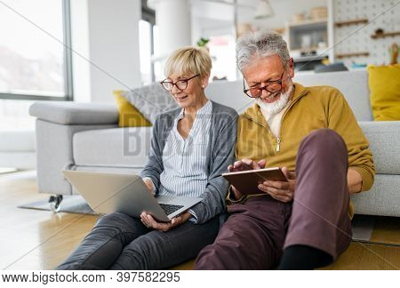 Cheerful Senior Couple Using Technology Devices And Having Fun At Home
