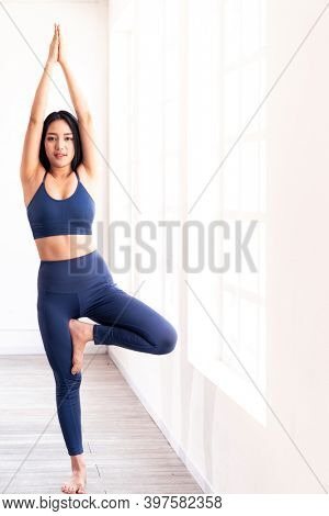 Portrait of sporty attractive asian woman practicing on standing tree pose in yoga lesson. Work out fitness healthy lifestyle concept