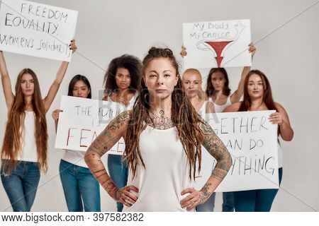 Young Caucasian Tattooed Woman With Dreadlocks Looking At Camera. Group Of Diverse Women Holding Pro