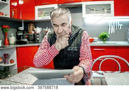 An Elderly Man With A Tablet Reads The News.
