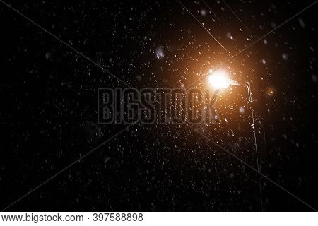 The First Snow In The Night Sky Against The Background Of The Lighting Pole.