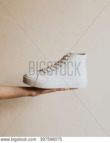 Hand holding white high top sneakers