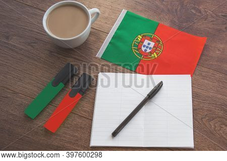 Portuguese National Flag, Pen, Notebook, Markers And Coffee Cup On Wooden Table, Foreign Language Le