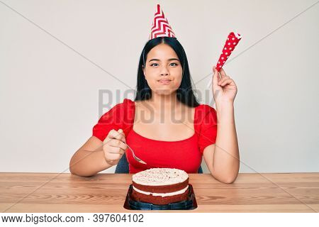 Young asian girl celebrating birthday with cake puffing cheeks with funny face. mouth inflated with air, catching air.