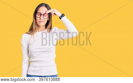 Beautiful brunette young woman wearing casual white sweater and glasses pointing unhappy to pimple on forehead, ugly infection of blackhead. acne and skin problem