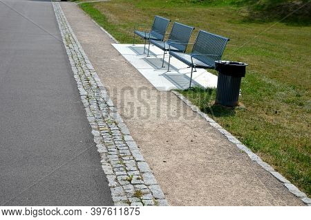Metal Modern Park Bench With A Metal Lightening Structure On One Leg Stands In The Park In Rest Area