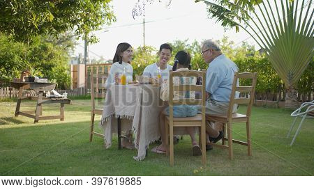 Asian Family Celebration Pizza Party Outside In The Backyard. Happy Family Having Festive Dinner Or