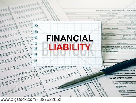 Notepad With Text Financial Liability Lying On Financial Tables With A Pen