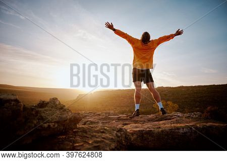 Rear View Of Young Man Standing With Arms Outstretched At Mountain Top During Morning Sunrise. Conqu