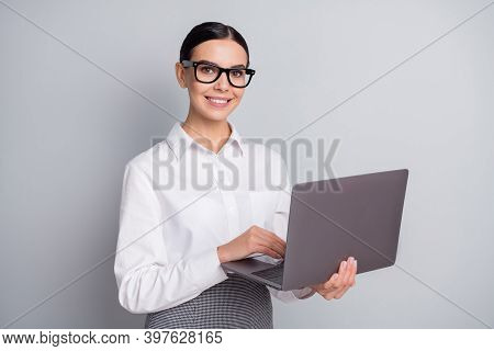Photo Of Cheerful Freelancer Lady Hold Netbook Look Camera Wear Spectacles White Shirt Isolated Grey