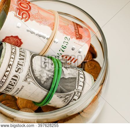 Russian Rubles, Us Dollars And Metal Coins In A Glass Jar Isolated On A Light Background. Store And