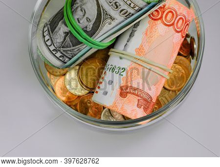 Russian Rubles And Us Dollars Rolled Up In A Tube, Metal Coins In A Glass Jar Isolated On A Light Ba