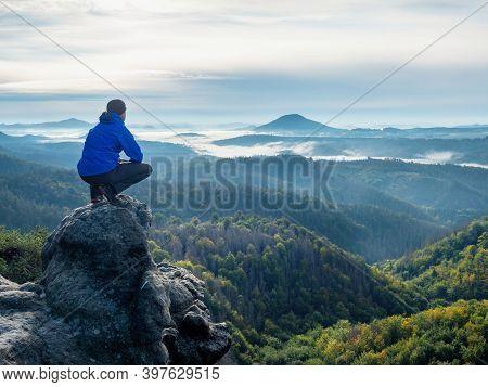 Hiker Sit On Cliff And Looking Beautiful Landscape. Tourist Watching To Autumn Sun At Horizon . Beau
