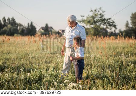 Happy Senior Man Grandfather With Cute Little Boy Grandson Playing In Field. Happy Child With Grandf