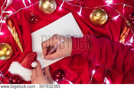 Write A Wish List For Santa With A Red Pen On A Blank White Sheet. Red And Gold Christmas Balls And