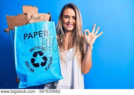 Young beautiful blonde woman recycling holding paper recycle bag full of paperboard doing ok sign with fingers, smiling friendly gesturing excellent symbol